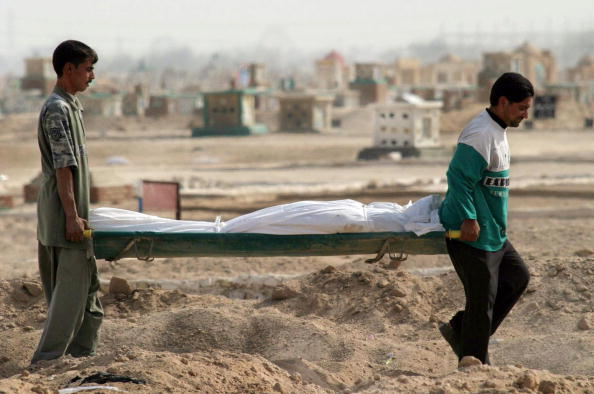 Iraqi workers carry a body to be buried - Getty