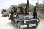 Two black jeeps carrying masked, combat camoflauge wearing al Shabaab militants.
