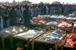 Khar, PAKISTAN: Deputy chief minister of Pakistan's North West Frontier Province Siraj-ul-Haq (L) and tribesmen offer funeral prayers in front of dead bodies who were killed in army operation in Khar, the main town in Bajaur tribal agency, 30 October 2006. Pakistani helicopter gunships destroyed an Islamic school allegedly used as an Al-Qaeda-linked training camp near the Afghan border, killing up to 80 suspected militants, officials said. AFP PHOTO/STR (Photo credit should read STR/AFP/Getty Images)