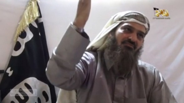 AQAP commander Saeed al Shehri, with a full, greyingbeard and white headress, gesticulates in front of a white background and black al Qaeda flag.