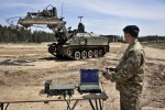 A soldier uses a games consol style controller to control a Terrier armoured digger, which is controlled by remote control during an unveilling at the Defence Armoured Vehicle Centre, Bovington, Dorset.