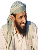 A bearded Nasser al Whuhayshi sits smilling wearing a white tunic and pale green, patterned headress.