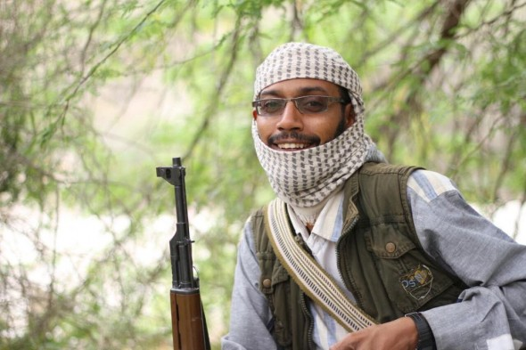 Said Bafaraj sits smiling in front of tree branches, holding a Kalashnikov rifle and with his head partly covered with a scarf. He is wearing spectacles.
