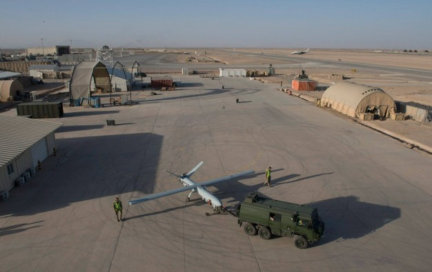 Watchkeeper made ready for take-off at Camp Bastion, Afghanistan. The grey aircraft is being toed in a semi-circle by a green six wheel vehicle. Two men in combat fatigues and high-visibility vests are at each wingtip, walking with the turning aircraft.