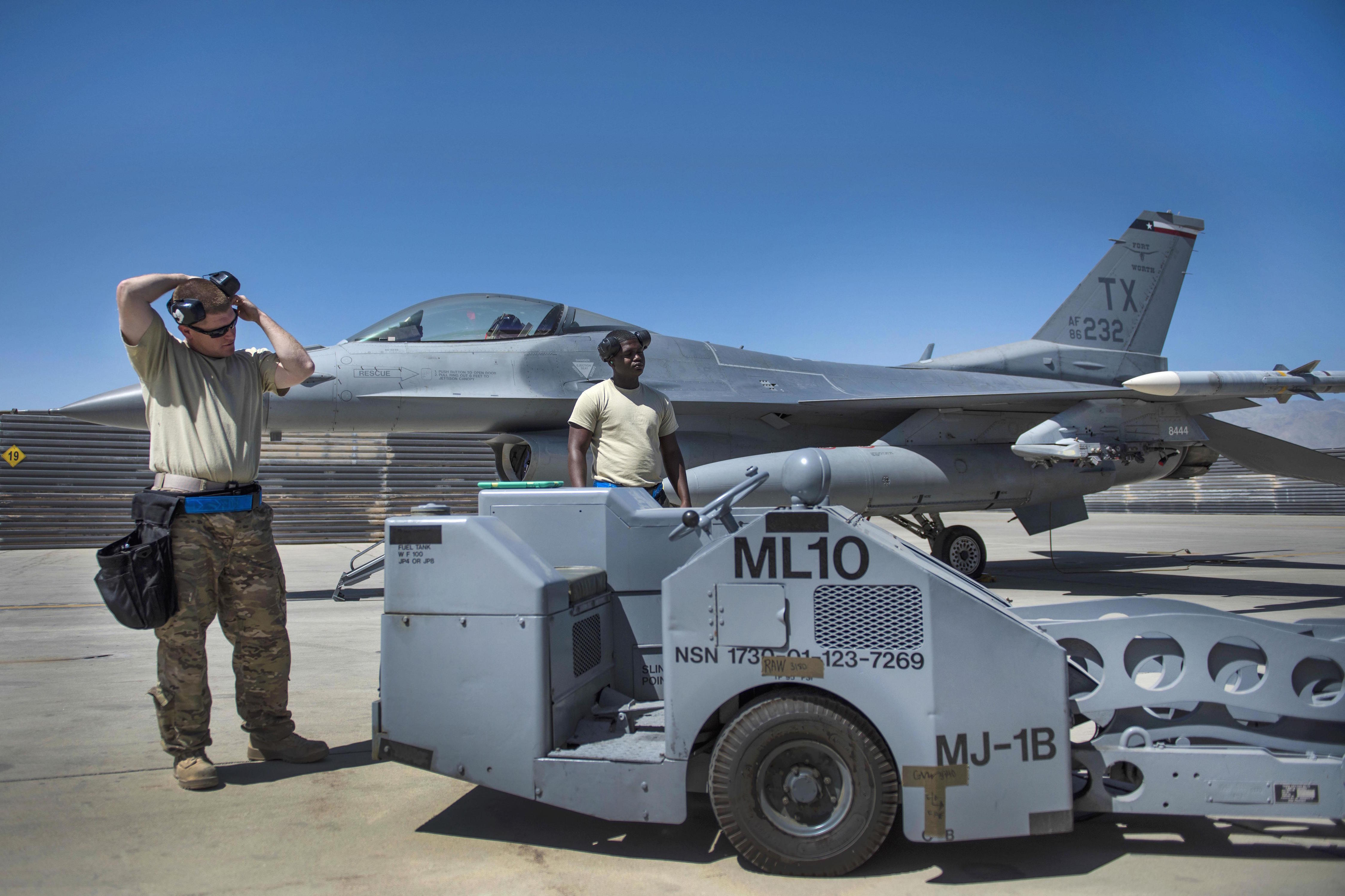 Air Force Tech. Sgt. Joseph McCullough, left, and Senior Airman Clarence Williams prepare to load two guided bombs on an F-16C Fighting Falcon aircraft at Bagram Airfield, Afghanistan, June 7, 2016. McCullough and Williams are weapons maintainers assigned to the 455th Expeditionary Aircraft Maintenance Squadron. Air Force photo by Senior Airman Justyn M. Freeman